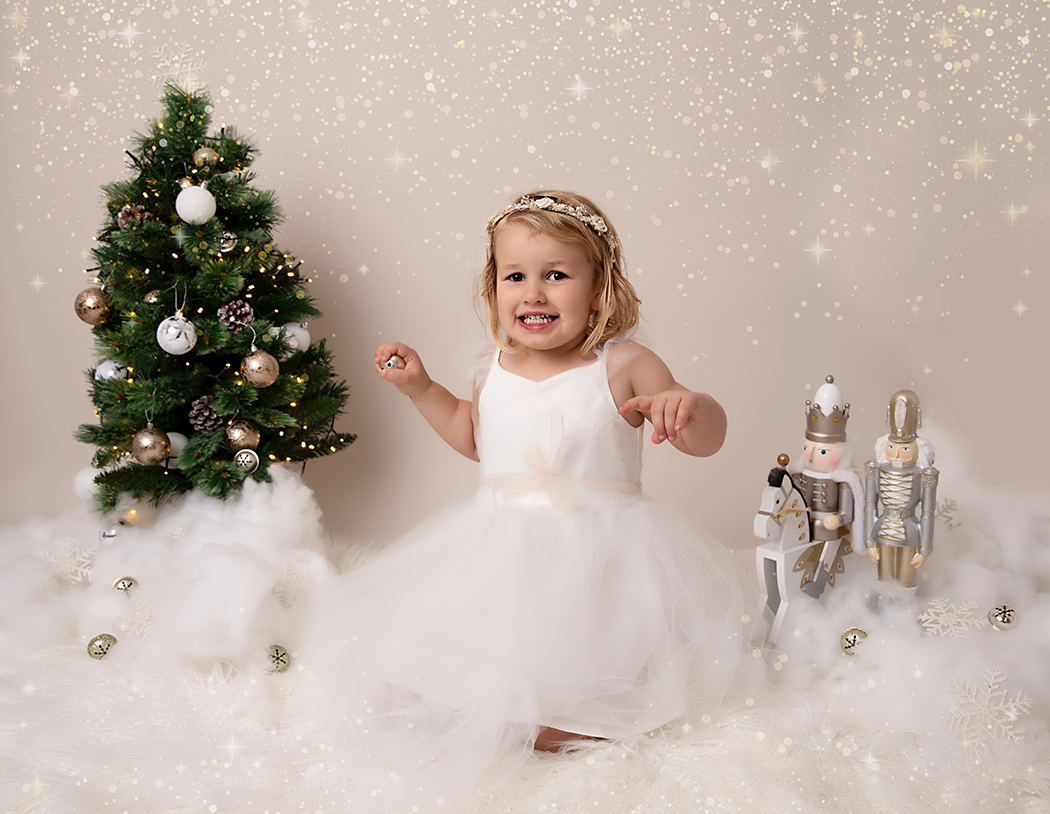 Young girl at her Christmas photoshoot playing with a jingle bell and smiling