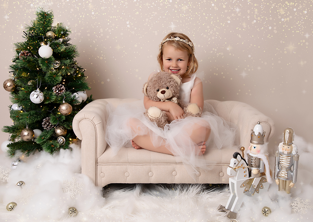 3 year old girl at her Christmas photoshoot sat on a miniature sofa cuddling her favourite teddy bear